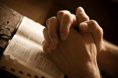 Praying hands on an open bible